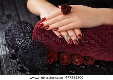 beautiful red manicure with roses and towel on the black wooden table