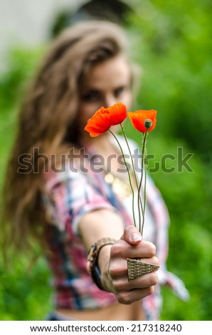 Beautiful red poppy flowers in women hands - stock photo