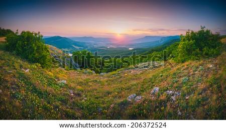 Beautiful red sunrise above the Crimea mountain valley. Panorama. - stock photo
