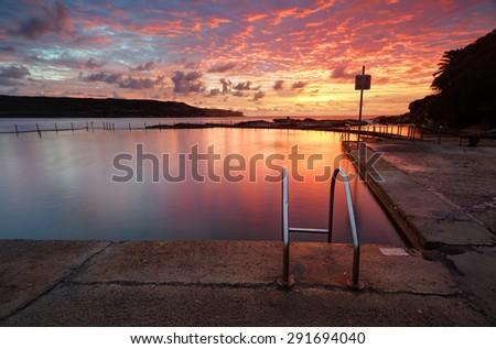 Beautiful red sunrise over Malabar Ocean Rockpool in Long Bay near Sydney Australia - stock photo