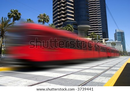 Beautiful red trolley moving fast through downtown - stock photo
