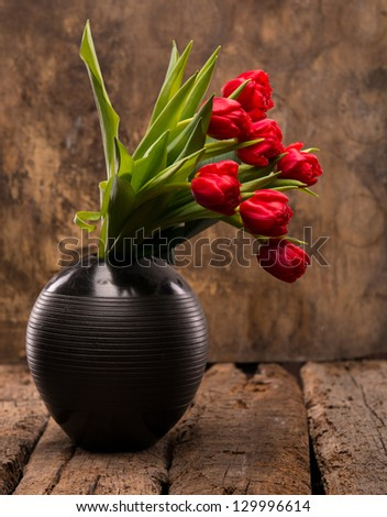 Beautiful red tulips in black vase on a wooden background - stock photo