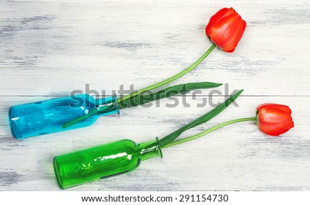 Beautiful red tulips in vases on wooden background - stock photo