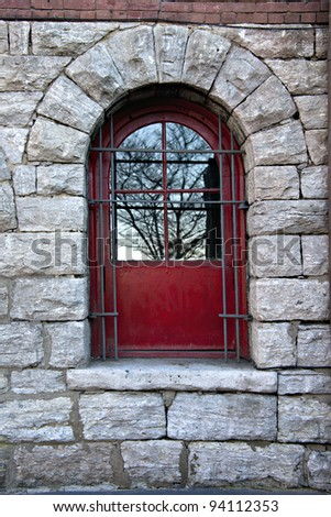 Beautiful red window or door in old stone wall with steel security bars and reflections of trees - stock photo