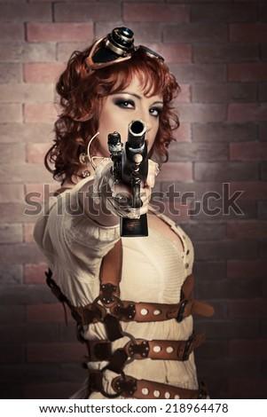 Beautiful redhair steampunk girl aiming a gun - stock photo