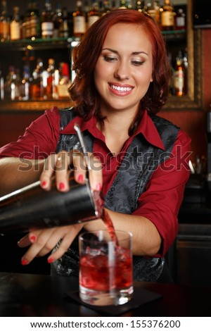 Beautiful redhead barmaid making cocktail - stock photo