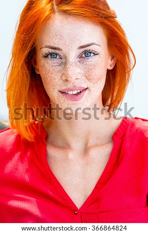 Beautiful redhead freckled woman smiling seductive, biting lips - stock photo