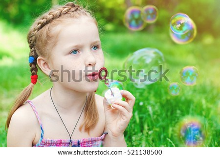 Beautiful redhead Girl blowing Soap Bubbles in the green grass in Summer - Child with Red Hair Outdoor