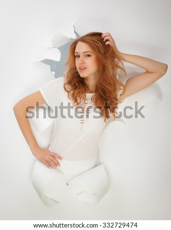 Beautiful redhead girl in a white dress in a hole in the paper.