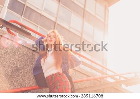 Beautiful redhead girl in blue jacket posing in an urban context. Backlight. - stock photo