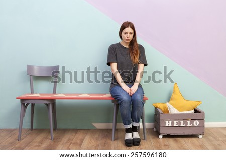 Beautiful redhead girl left alone on a two seats bench. Looking sad at the camera. Hello box. - stock photo