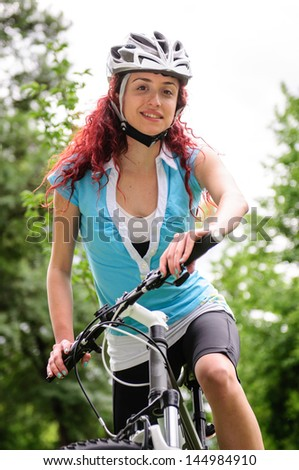 Beautiful redhead girl posing with a bicycle