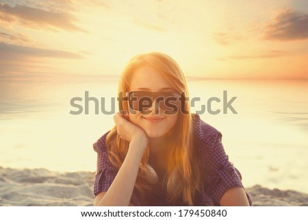 Beautiful redhead girl with headphones at beach sand in sunrise time. - stock photo