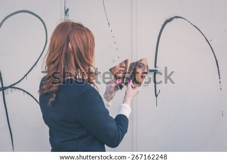 Beautiful redhead girl with long hair and blue eyes looking at herself in a broken mirror - stock photo