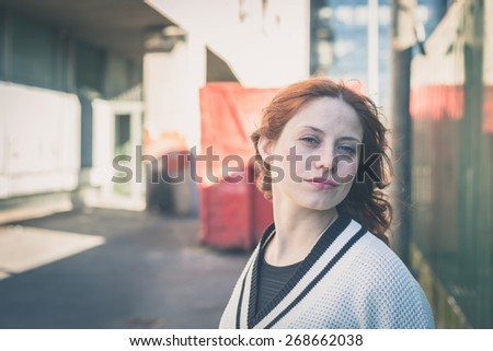 Beautiful redhead girl with long hair and blue eyes posing in an urban context