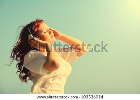 beautiful redhead girl with long hair enjoys music with headphones in the sky with your eyes closed - stock photo