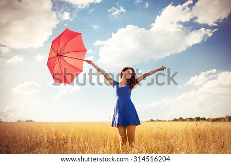 Beautiful redhead girl with umbrella at autumn countryside  - stock photo