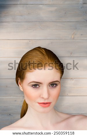 Beautiful redhead looking at camera against wooden planks - stock photo