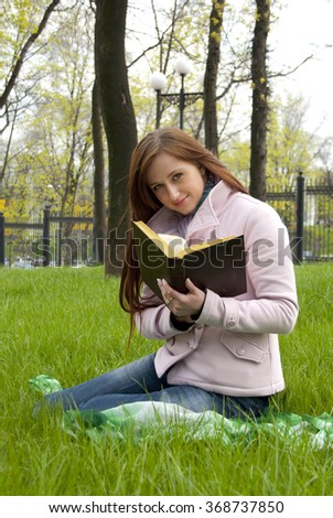 Beautiful redhead woman reading book on a meadow