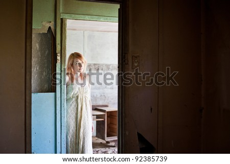 Beautiful redhead woman wearing long flowing dress standing in derelict abandoned house