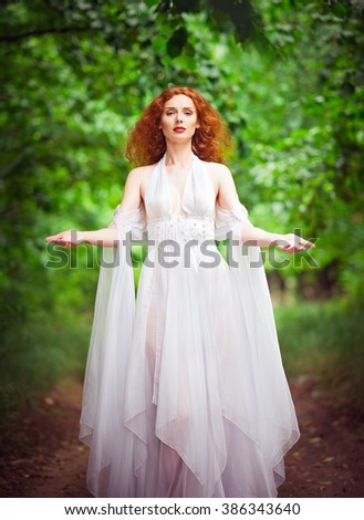Beautiful redhead woman wearing white dress in the forest - stock photo