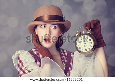 Beautiful redhead women with clock. Photo in retro style with bokeh at background.