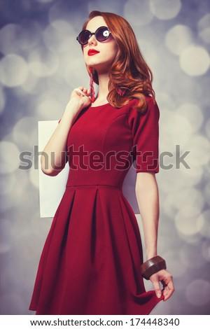 Beautiful redhead women with shopping bag - stock photo