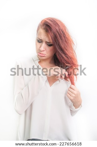 Beautiful redhead young female cutting her hair with a sad expression suggesting hair loss - stock photo