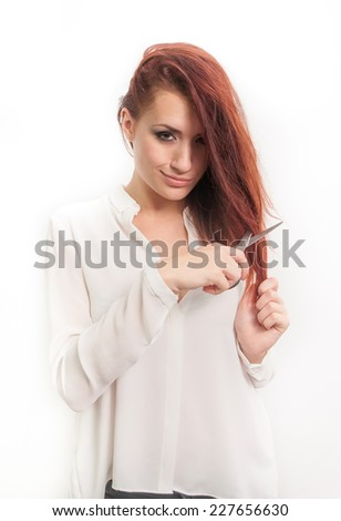 Beautiful redhead young female cutting her hair with a smart confident expression suggesting hair loss
