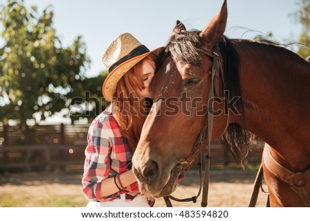 Beautiful redhead young woman cowgirl standing and kissing her horse