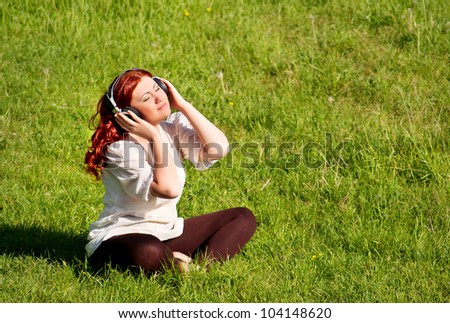 beautiful redhead young woman listening to music with headphones on nature, outdoors, on grass lawn - stock photo