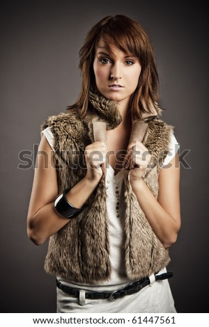 beautiful redheaded girl posing in fur vest - stock photo