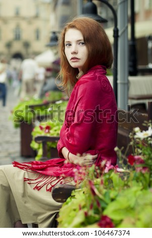 beautiful redheaded woman resting on the streets of the beautiful city - stock photo
