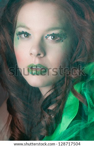 Beautiful redheaded woman with green highlighted makeup for St Patrick's day - stock photo