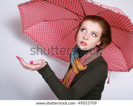 Beautiful redheaded young women with pink umbrella - stock photo