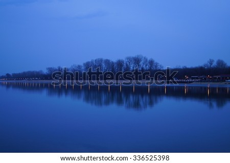 Beautiful reflection of the trees and lights in the lake Ada Ciganlija at the blue hour in winter, Belgrade, Serbia