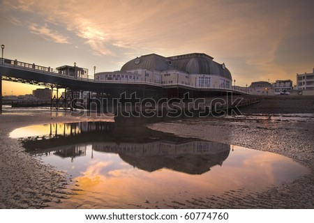 Beautiful reflections of pier in low tide water pool at sunset