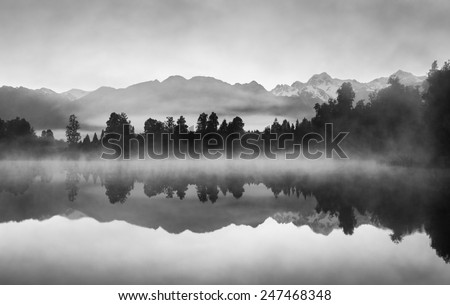Beautiful reflections of Southern Alps at Lake Matheson, New Zealand, in the early morning mist, in black and white. - stock photo