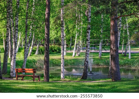 Beautiful relax place near pond in summer park - stock photo