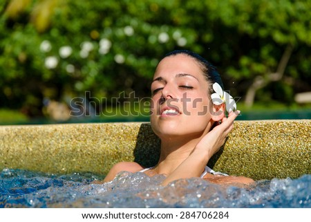 Beautiful relaxed woman enjoying spa pool at resort in Thailand. Relaxing outdoor jacuzzi. - stock photo