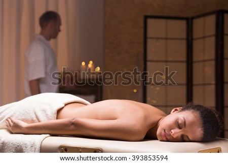 Beautiful relaxed woman lying on a couch and waiting for massage in spa resort - stock photo