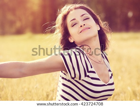 Beautiful relaxing woman enjoying fresh air in sunny summer day on nature background with closed eyes - stock photo