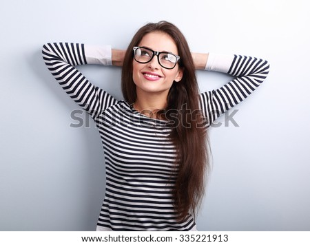 Beautiful relaxing woman in glasses looking up with thinking look on blue background with empty copy space