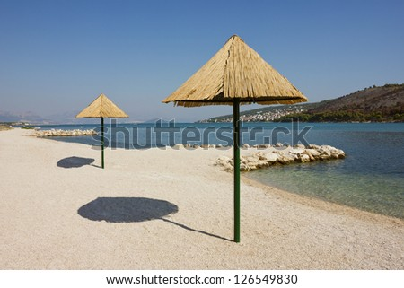 Beautiful remote beach on Adriatic seacoast near Trogir in Croatia with crystal clear calm inviting water. - stock photo