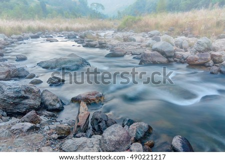 Beautiful Reshi River water flowing through stones and rocks at dawn, Sikkim, India. Reshi is one of the most famous rivers of Sikkim flowing through the state, Shot under fog.