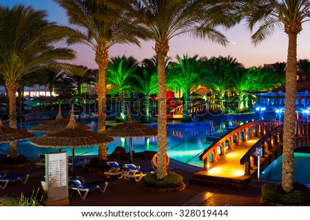 Beautiful resort place - illuminated swimming pool with tropical palm tree garden. Multicolored summertime vibrant vertical outdoors image. Egypt. Sharm-el-sheikh - stock photo