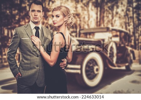Beautiful retro couple against vintage car - stock photo