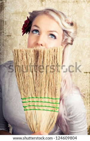 Beautiful retro nineteen fifties housewife sitting daydreaming looking up at the ceiling with a faraway expression while holding a straw broom concealing the lower portion of her face - stock photo
