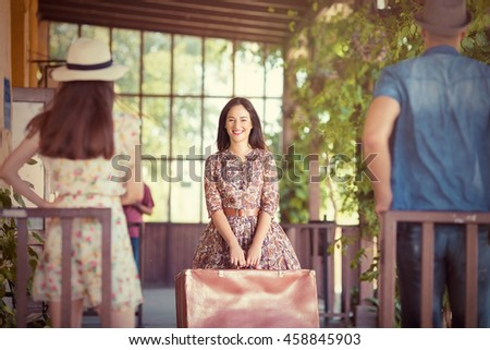 Beautiful retro-styled young woman is arriving at the train station. She is holding a suitcase and smiling to her friends waiting for her.