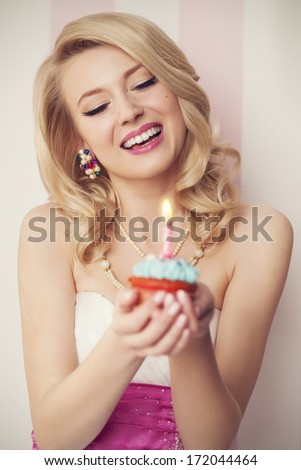 Beautiful retro woman celebrate with blue muffin - stock photo